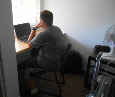Picture for his motherof John studying in his new apartment.